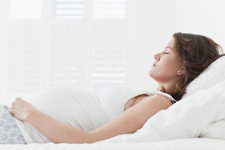 pyjama: Pregnant woman sleeping on bed