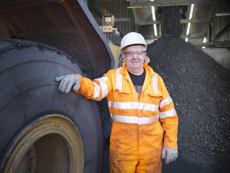 leaning on the truck: Worker standing by truck at coal mine LANG_EVOIMAGES