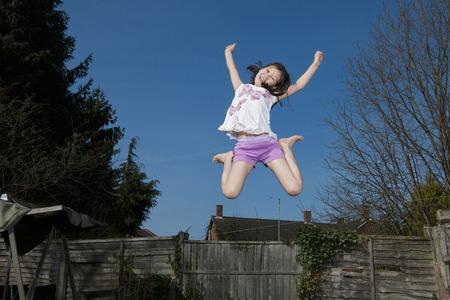legs apart: Smiling girl jumping for joy outdoors