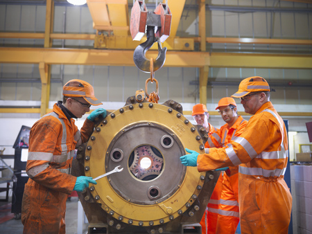 Engineer teaching apprentices in factory