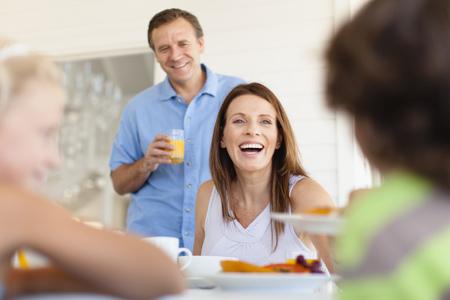 niños platicando: Familia comiendo juntos en la mesa