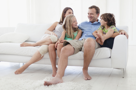 pas: Family relaxing together on sofa