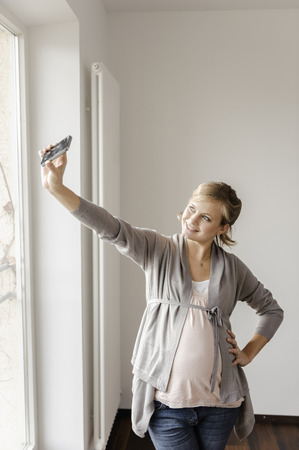 Pregnant woman taking picture of herself LANG_EVOIMAGES