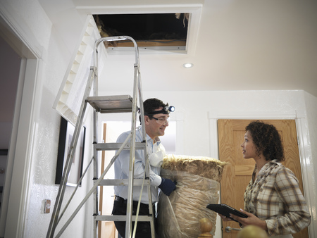 women's issues: Worker carrying insulation to attic