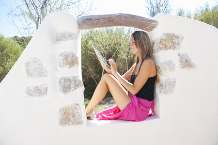 Woman using tablet computer outdoors LANG_EVOIMAGES