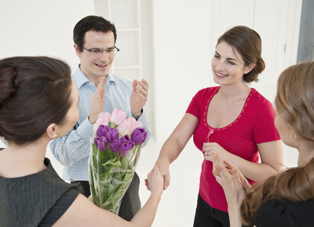 accomplishes: Business people giving colleague flowers LANG_EVOIMAGES