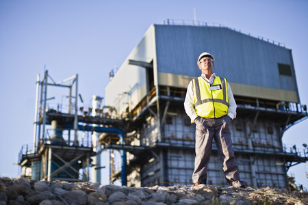 Worker standing at chemical plant LANG_EVOIMAGES