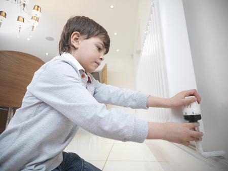 profile measurement: Boy adjusting radiator in kitchen LANG_EVOIMAGES