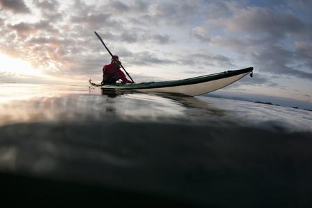 Man kayaking on still lake