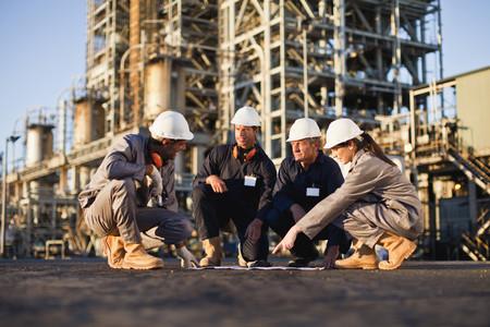 Werknemers met blauwdrukken bij olieraffinaderij