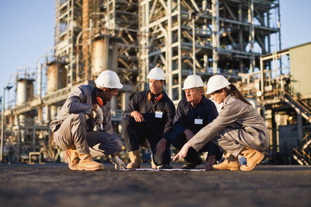 review: Workers with blueprints at oil refinery