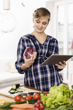 conscience: Woman using tablet computer to cook
