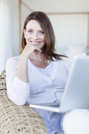 pcs: Woman using laptop in armchair LANG_EVOIMAGES