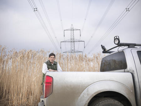 leaning on the truck: Farmer with truck in elephant grass