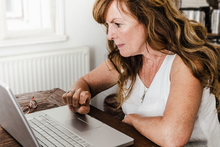 uses: Older woman using laptop in kitchen