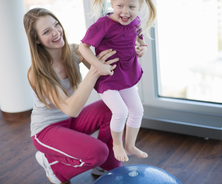 faiths: Girls playing with exercise ball in gym LANG_EVOIMAGES