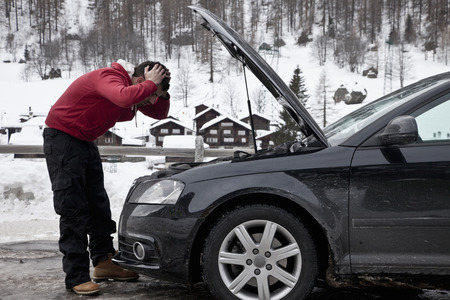 hardships: Frustrated man checking car engine