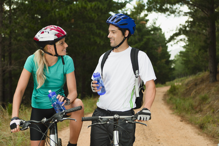 Couple drinking water on mountain bikes LANG_EVOIMAGES