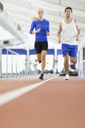 Couple running on indoor track in gym LANG_EVOIMAGES