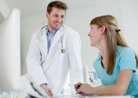 Doctor talking to receptionist in office LANG_EVOIMAGES