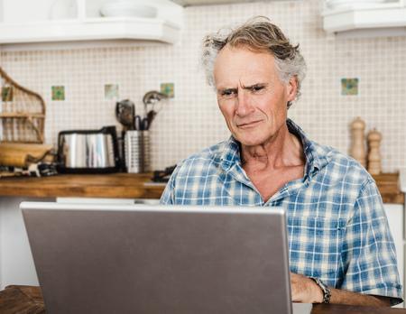 Older man using laptop in kitchen LANG_EVOIMAGES