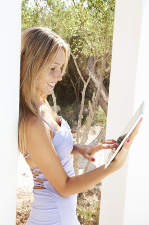 web portal: Woman using tablet computer outdoors LANG_EVOIMAGES