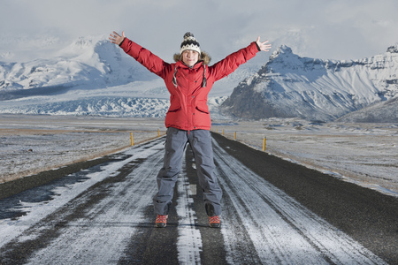 Woman standing on snowy road LANG_EVOIMAGES