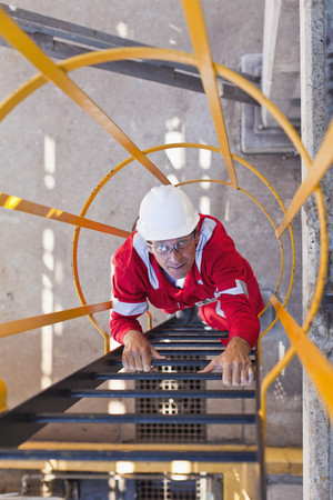 ascends: Worker climbing ladder at oil refinery