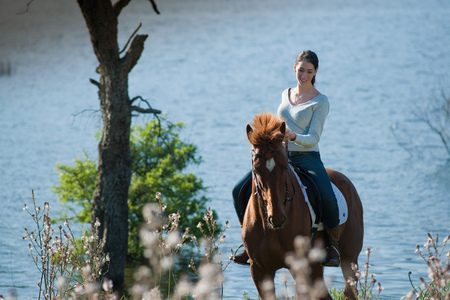 Woman riding horse by rural lake