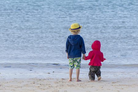 Children holding hands on sandy beach LANG_EVOIMAGES