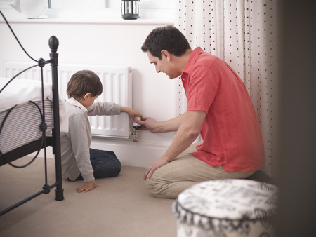 45 50 years: Father and son adjusting radiator