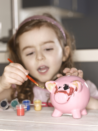 held down: Girl painting piggy bank