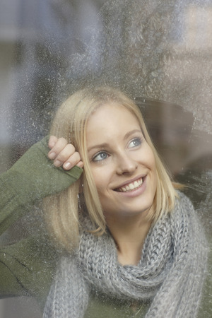 snows: Smiling woman standing at frosty window