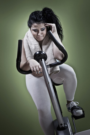 Woman using exercise bike at home LANG_EVOIMAGES