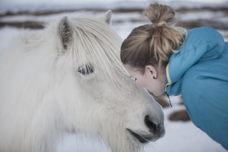 Woman kissing white horse in snow