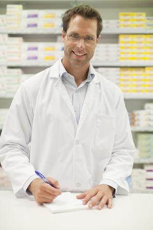 resolving: Pharmacist making notes at counter