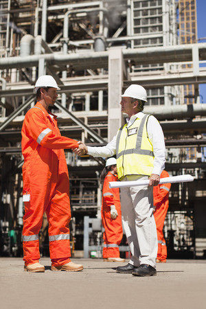 agrees: Workers shaking hands at oil refinery