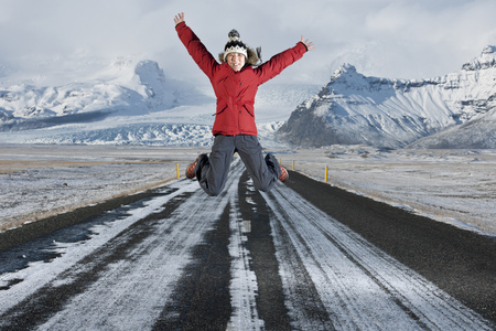 Woman jumping on road in snowy landscape