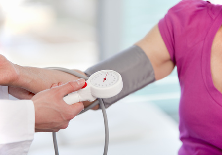 help section: Doctor taking womans blood pressure