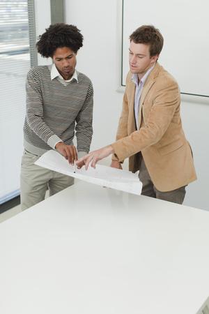interrogations: Businessmen examining blueprints