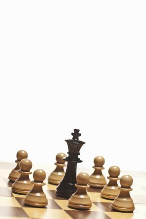 White pawns surrounding black chess king LANG_EVOIMAGES