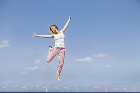 Woman jumping for joy over wind turbines LANG_EVOIMAGES