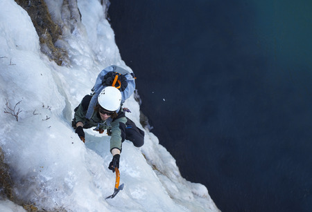 Climber scaling icy mountainside