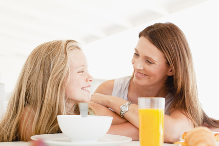 Mother talking to daughter at breakfast
