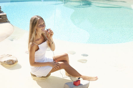 handsfree telephones: Woman listening to headphones by pool