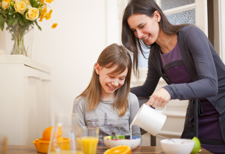 Woman pouring milk for daughter at table