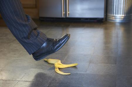 stepping: Businessman stepping on banana peel