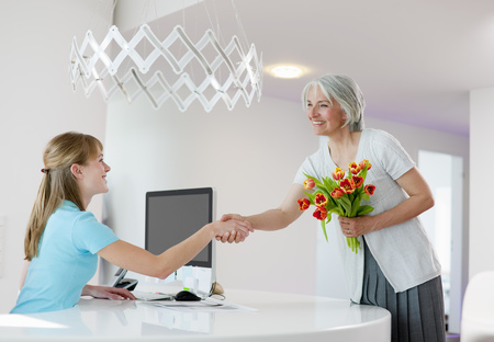 Receptionist shaking womans hand