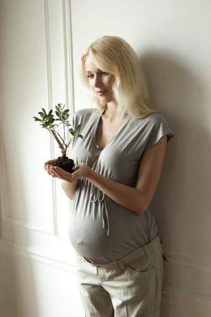 Pregnant woman holding sapling LANG_EVOIMAGES