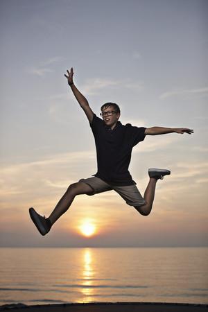 sun energy: Teenage boy posing in mid-air